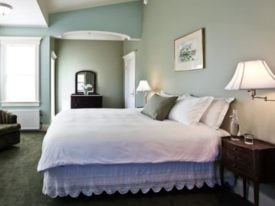 green room with bed and white bedspread