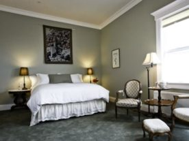 bed with white bedspread in green room