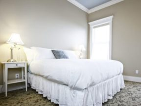 bed with white bedspread and lamp on nightstand