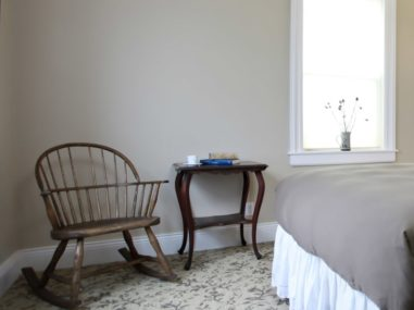 small rocker and brown table near bed