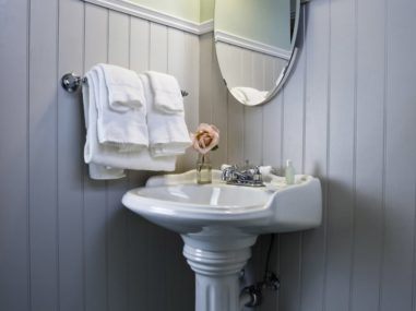 white pedestal sink with white towels and mirror
