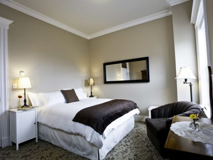 bed with white linens and brown cover