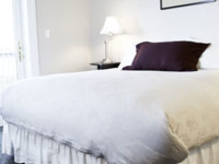 bed with white bedspread and brown pillow