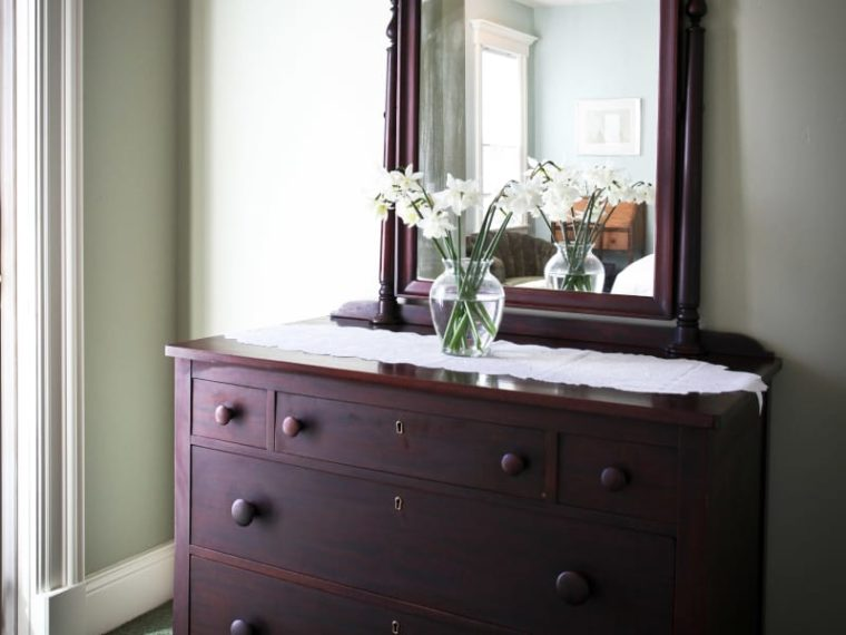 brown dresser with mirror and vase of white flowers