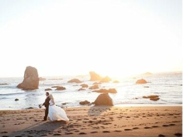 bride and groom walking along sandy beach