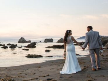 bride and groom walking on beach looking at each other