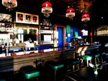 bar with red lights and green stools