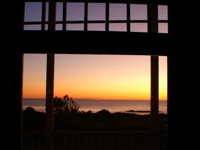 view from inside looking out at water with sunrise or sunset