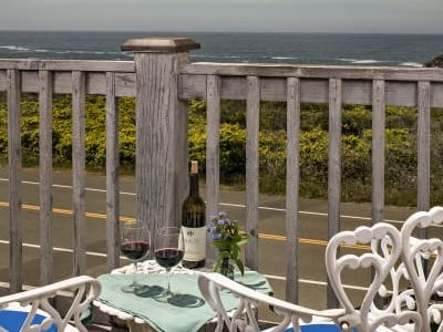 balcony overlooking road and water with white chairs, bottle and glasses of wine